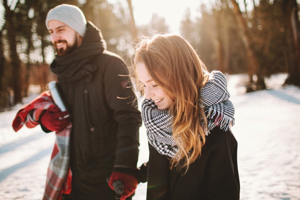Young hipster couple walking in winter forest hand in hand with tea in thermos