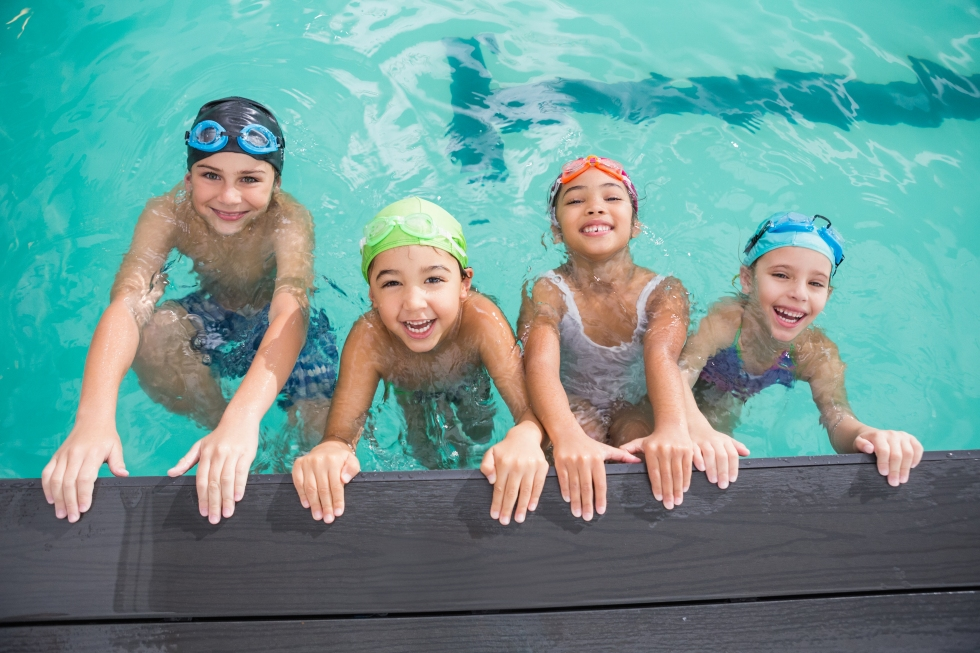 Cute swimming class in the pool at the leisure center